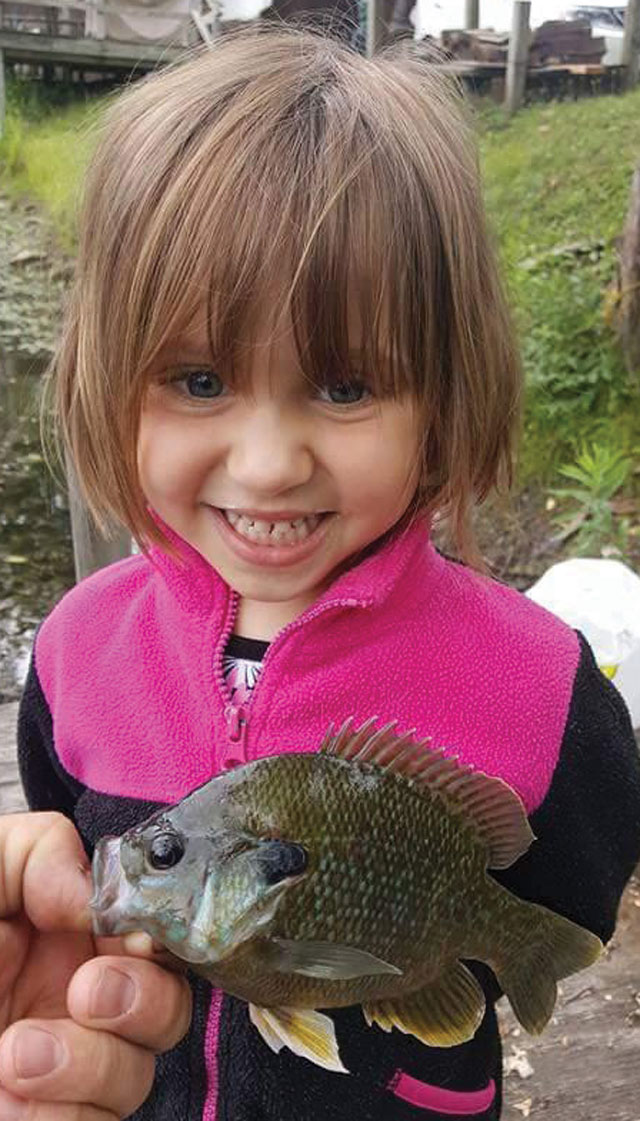 Annabelle Woodson doesn't quite know what to think about this little bluegill caught at the Giant Goose Ranch.