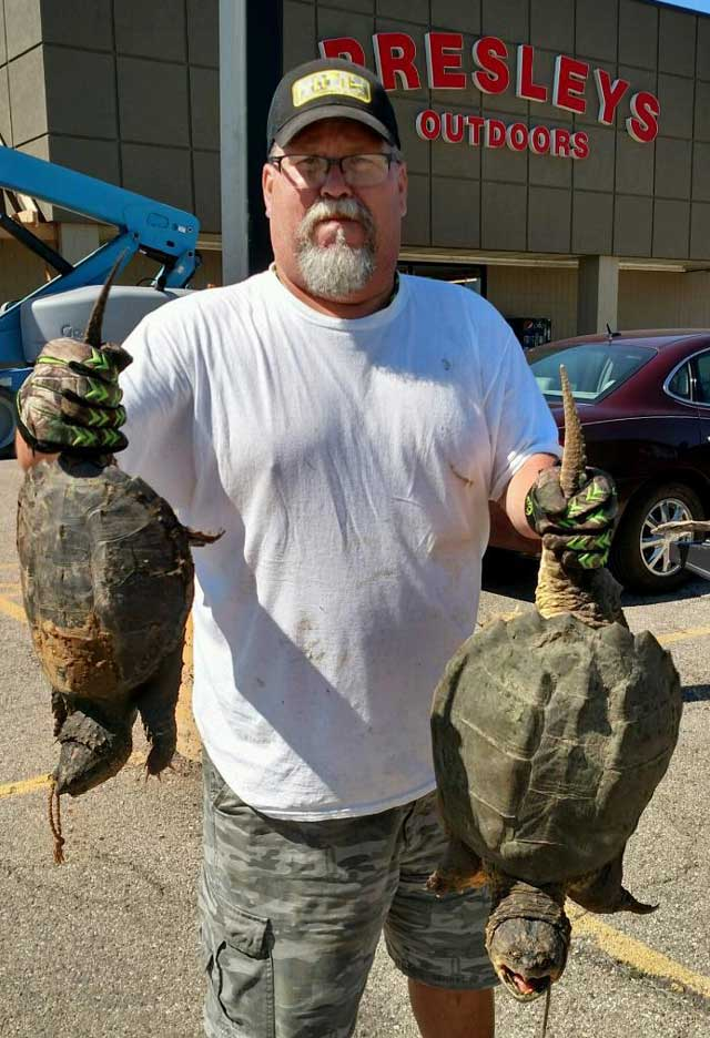 Chef Todd Kent hoists two turtles he caught recently in central Illinois