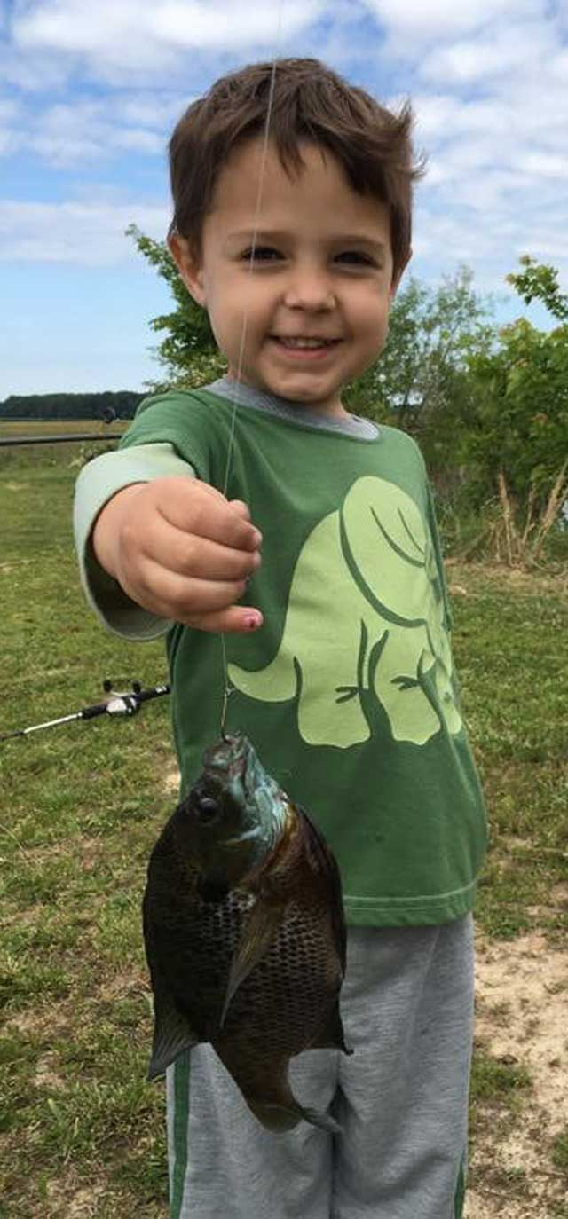 Ethan Powers of Moline caught his first fish last Saturday in his grandfather Carl's lake south of Nashville