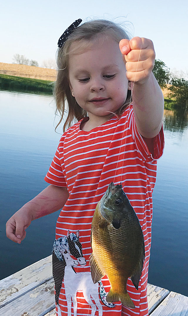 Isla Putney of Elmwood holds up her first fish