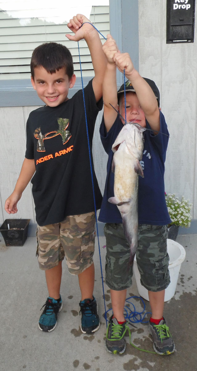 Jet and Cash hold up their big catch from Mark Twain Lake in Missouri. Photo courtesy of TIMBER RIDGE RESORT.