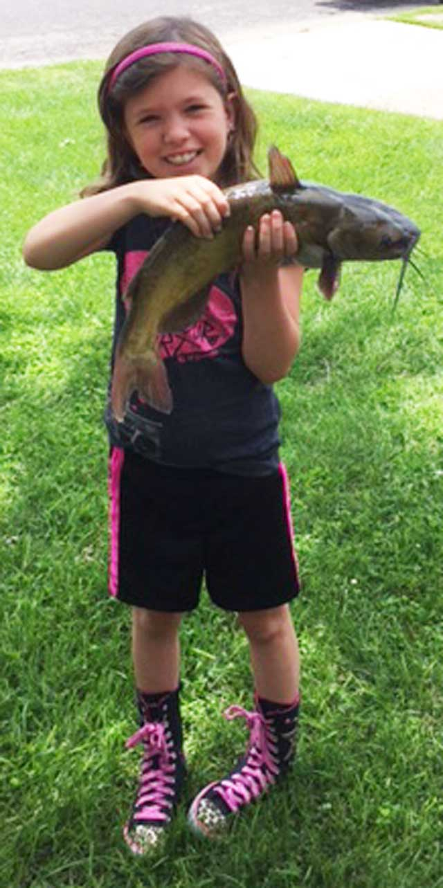 Jordain Reardon, 7, hoists a channel catfish she caught at the Wilmor Sportsmen Club near Morton.