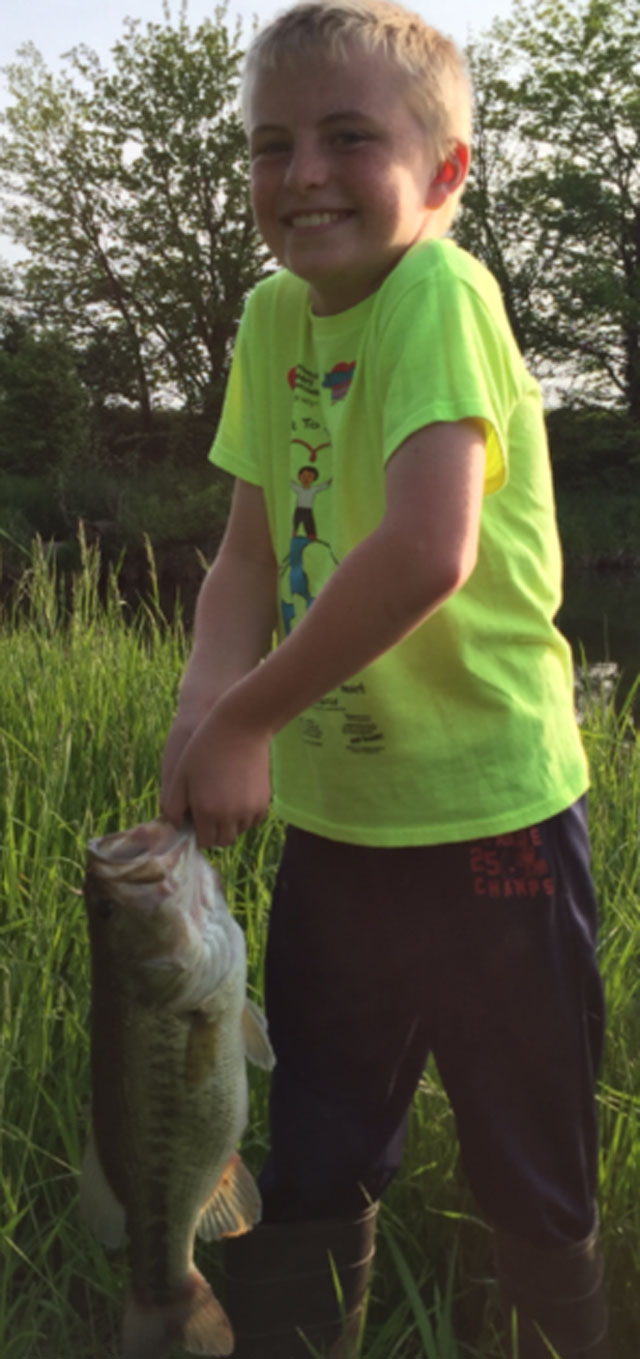 Kaden-Griswold-of-LeRoy-is-excited-after-catching-his-biggest-bass-during-a-June-fishing-trip.