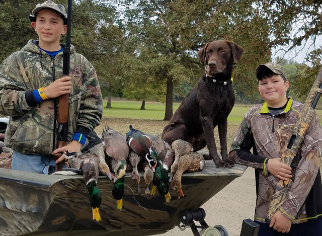 Kadin Gensler and Sam Salz of Toluca pose with Deke after a very good youth season opener in Woodford County along the Illinois River.