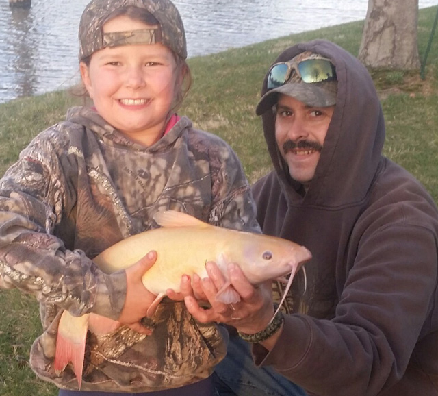 Kami Roberson, 8, of Peoria caught this albino catfish in a private pond while fishing with Jack Jones (right).