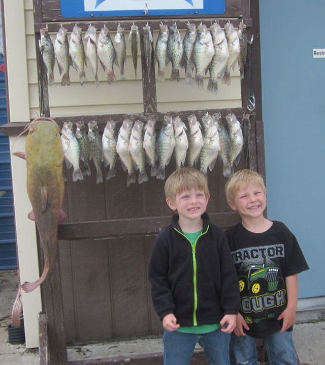 Landen Sells and Korbin Stuart fished with their fathers in early May on Mark Twain Lake and caught these two limits of crappie and a nice flathead. Photo courtesy of SOUTH FORK RESORT.