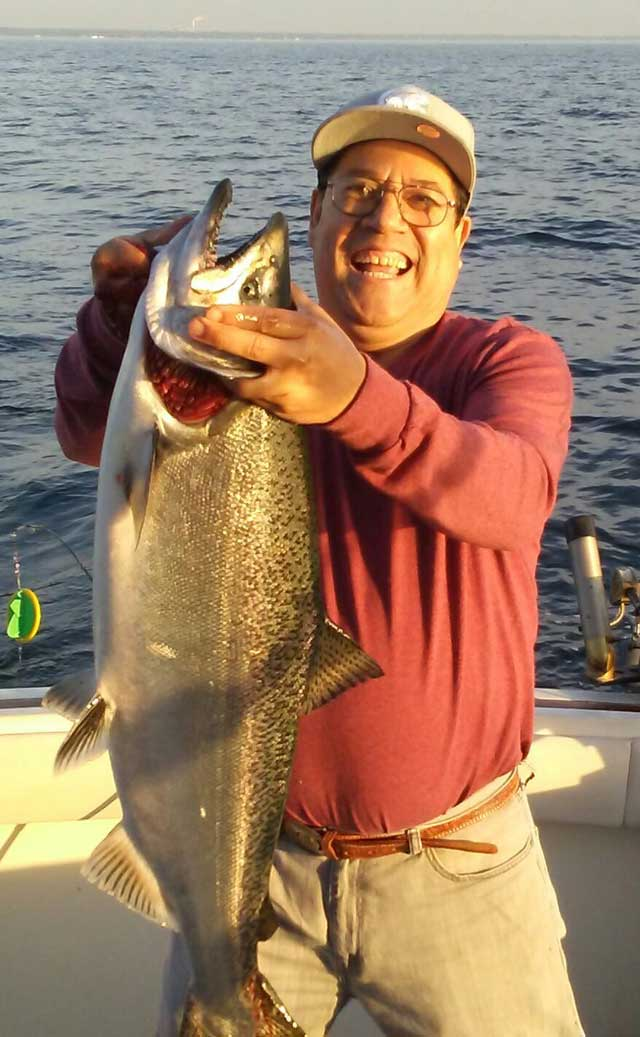 Oscar-Cisneros-of-Chicago-is-all-smiles-after-catching-this-20-pound-Chinook-salmon-while-fishing-aboard-Noble-II-with-Captain-Dale-Florek.