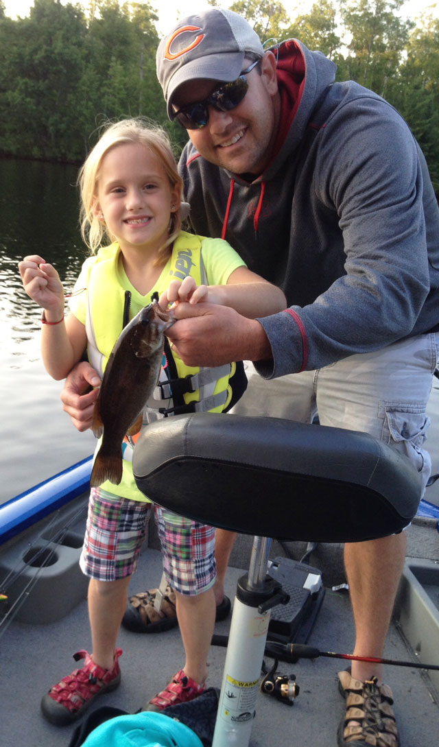 7 year old  from Peoria catches here first small mouth bass from the Chippewa Flowage in Wisconsin.