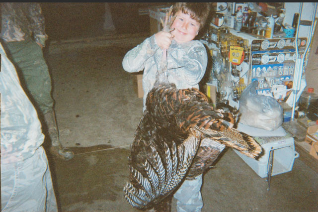 boy hoists a 22-pound wild turkey shot last spring in southern Illinois.